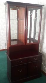 Tall, dark display cabinet with glass shelves