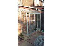 Glass-pane greenhouse. Stands against a wall with entrance door - one pane missing in door