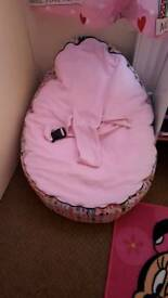 A girls pink bean bag suitable from birth