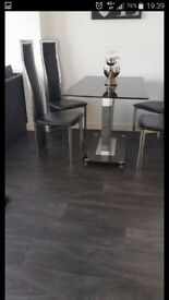 Black and siver dining room table with 4 siver and black chairs