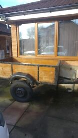 Trailer. Wooden solid trailer with 2 good tyres approx 5ft 6 long x 3ft 6 wide.