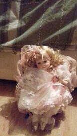 Porcelain dolly girl with a teddy bears on a wood chair.