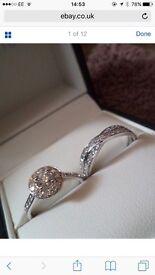 Platinum 1 carat diamond cluster bridal set engagement and wedding ring set .