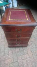 An ox blood red leather filing cabinet