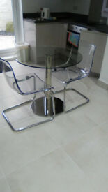 Glass table and four clear perspex chairs
