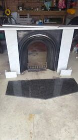 Marble fireplace surround, cast iron insert and grate and black granite hearth