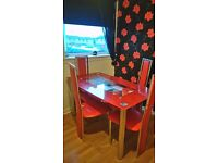Red Glass dining table and four red leather chairs