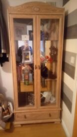 Solid wood display cabinet with mirrored back glass shelves and one drawer.
