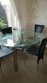Glass extending dining table and 4 black leather chairs