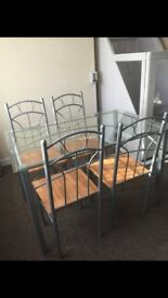 Glass dining table with 4 chairs. Brilliant condition