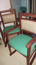 Pair of sturdy wooden reupholstered chairs with arms and sliders.