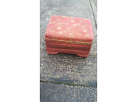 orangy red patterned foot stool with lift up lid and padded top