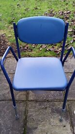 Blue cushioned commode chair with removable waste bucket and lid