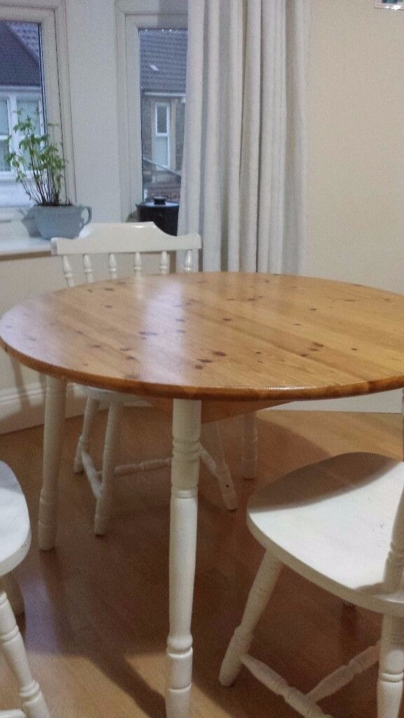 Round Wooden Table And Three Wooden Chairs