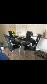 Glass table with 4 chairs and a side unit