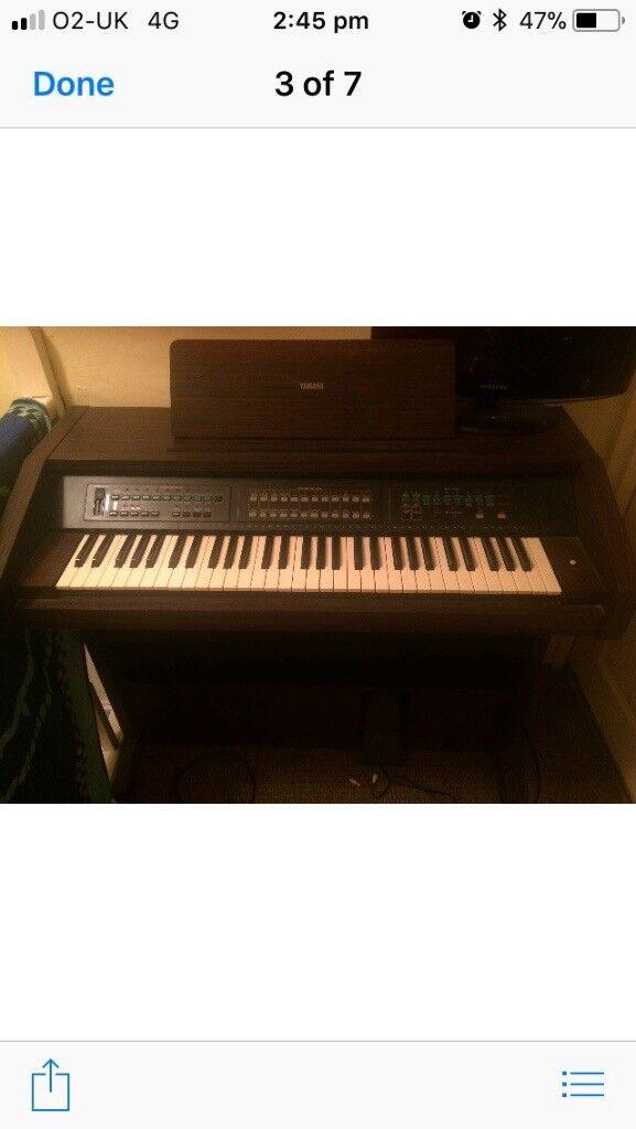 Yamaha Organ and storage stool with music books