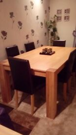 Beautiful light oak dining table, and 6 brown chairs, excellent condition, heavy, legs dismantle .
