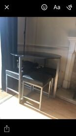 Black round glass dining room table and 4 chairs