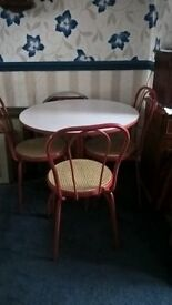 a red painted metal framed bistro set - table and three chairs