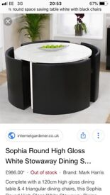 White round table and four black leatherette comfortable chairs