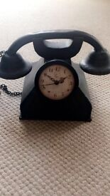 Old style steel telephone with clock.