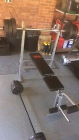 Bench press (adjustable with leg extension). Two barbells. 70kg weight plates. 1-4.5kg Dumbell set.