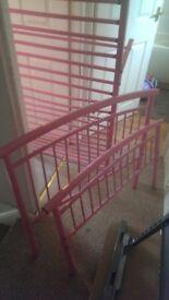 Metal framed single bed, pink coloured.