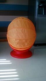 Red and orange ikea egg swivel chair with hood