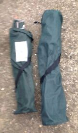 Two green camping chairs in protective sleeves