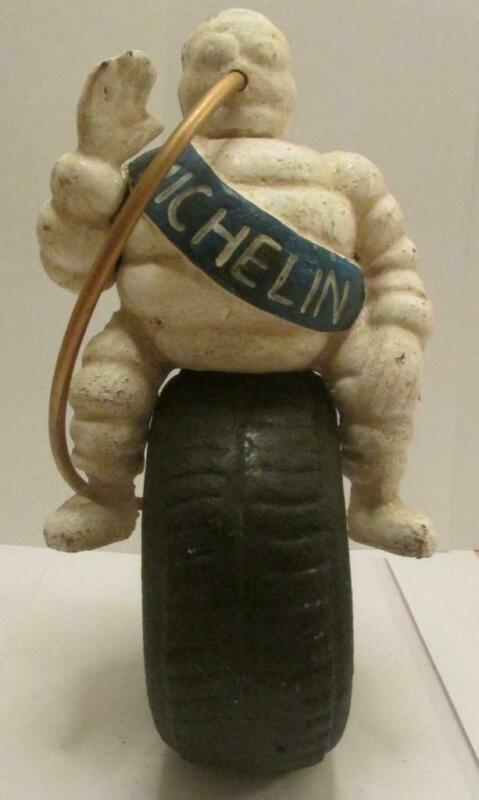 Michelin Man Sitting on a Tire with Hose Blowing Up The Tire