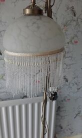 Standard lamp. Brass with scroll design and beaded glass shade.