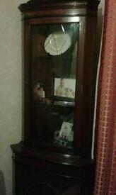 Dark wood glass corner unit with key corner unit has cupboard underneath