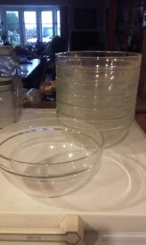 Seven plain round glass salad bowls that stack together when not in use.