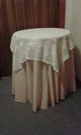 Round circular chipboard side table with peach floor length cloth and lace overclotj