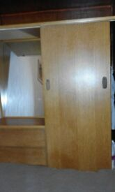 Wardrobe with combined shelves on side, with mirror above.