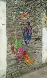 Dream catcher mobile has a multi coloured main web with 6 individual fish.