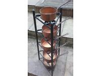 5 copper pans on a stand