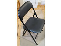 Nine black folding chairs - most unused. Steel tubular structure and plastic covered seats and back.