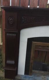 Mahogany, ornate fireplace with marble inset.