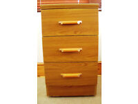 3 drawer (antique pine?) wood effect cabinet, chest of drawers on castors, wooden handles. £15 ovno.