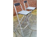 2 bar stools. Metal frame, black wooden seat and back-rest. Seat height 75cm. In very good condition