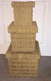 A nest of 3 square wicker baskets with lids