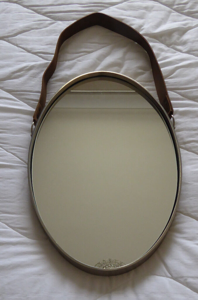 A collection of three John Lewis wall mirrors, two round and one oval