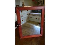 Dark wood bathroom cabinet with mirror.
