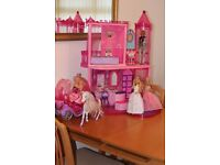 Barbie castle, plus horse and carriage, and four dolls.