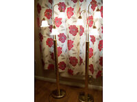 Two gold metal lamp stands, each with three glass shades