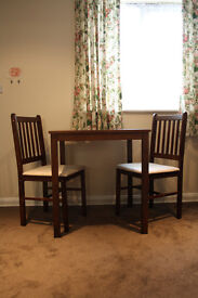 Compact dining table with two chairs in walnut and cream