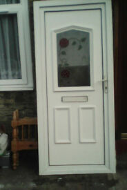 White upvc door with obscure glazed top panel with rose design