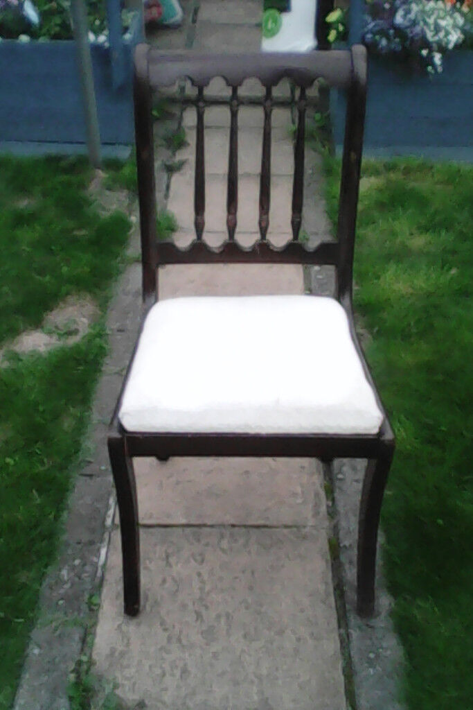 Four solid wood dining chairs ( one is a carver )