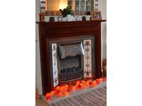 Ornamental cast iron fireplace and mahogany mantelpiece incorporating electric heater